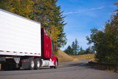 Red semi truck rig and trailer on autumn convoluted highway Stock Photography