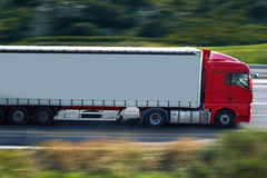 Red semi truck. Speed   semi truck on highway Stock Photo