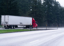 Red semi truck trailer on wide highway with trees Royalty Free Stock Photos