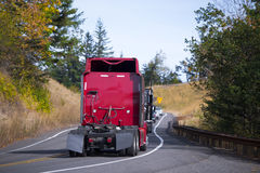 Red Semi trucks back convoy on winding fall road. A column of several modern semi trucks without trailers with spoilers, and mudguards, along with the other cars stock photography