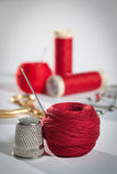 Red sewing kit. Still life with sewing theme in red, complete with thimble, thread, needle, scissors and more thread reels in the background Royalty Free Stock Photo