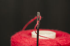 Red  sewing thread indented through the hole Royalty Free Stock Image