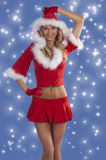 Red sexy christmas lady smiling. Sexy and beautiful blond young woman wearing a red christmas dress with hood and fur smiling Royalty Free Stock Image