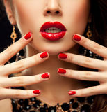 Red Sexy Lips and Nails closeup. Manicure and Makeup. Make up concept. Half of Beauty model girl's face  on Royalty Free Stock Photography