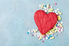 Red shape of heart and colorful drug pills on blue background top view. Pharmaceutical, cardiology and health care concept. Stock Images