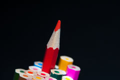 Red sharpened pencil among colorful crayons. stock photos