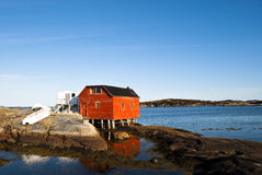 The Red Shed. Rugged Coastline showing a Red Shed on Stilts and Overturned Dory Royalty Free Stock Photos
