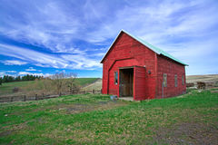 Red shed, green grass, blue sky. Royalty Free Stock Photo
