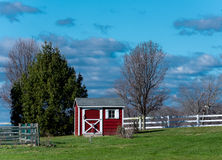 Red Shed. A red shed in green meadowland with blue sky and white clouds in the background Stock Images