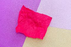 The red sheet of crumpled paper in the background of several colors: yellow, pink, purple. The red sheet of crumpled paper in the background of several colors Stock Photo