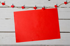 Red sheet of paper on a white wooden background with copy space. Royalty Free Stock Photo