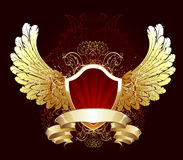 Red shield with golden wings. Red gilded shield decorated with gold feathered wings and a flexible golden ribbon Stock Photo