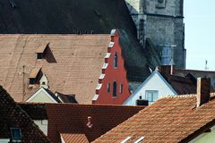 A red shield between the roofs of the original houses of an ancient town. In central Germany Royalty Free Stock Images