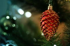 Red shining pine acorn cone hanging on a Christmas tree with blur bokeh background. New Year decoration prop. Copy space available for text, logo, product and stock image