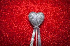 Red shiny background with silver hearts, love, Valentine`s Day, texture abstract background, romantic picture, suitable for adver Stock Photography