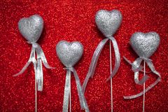 Red shiny background with silver hearts, love, Valentine`s Day, texture abstract background, romantic picture, suitable for adver Stock Photos