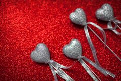 Red shiny background with silver hearts, love, Valentine`s Day, texture abstract background, romantic picture, suitable for adver Royalty Free Stock Photo