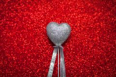 Red shiny background with silver hearts, love, Valentine`s Day, texture abstract background, romantic picture, suitable for adver Royalty Free Stock Photography