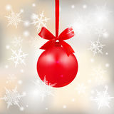 Red shiny ball with a bow on a beautiful Christmas background. Hanging on a ribbon among the snowflakes. Christmas tree Royalty Free Stock Photo