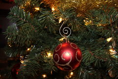 Red shiny christmas ornament on the tree. White lights, Red ornament ball, gold swirl, christmas tree Royalty Free Stock Photo
