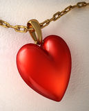 Red shiny heart pendant, with gold chain, on a white paper. Royalty Free Stock Image