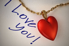 Red shiny heart pendant, with a gold chain, on white paper and t Royalty Free Stock Photo