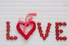 Red shiny hearts. On a white wooden background Stock Image