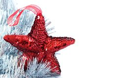 Red shiny star decoration with silver tinsel. Red shiny Christmas star decoration with silver tinsel on white background Royalty Free Stock Images