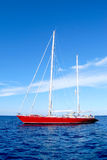 Red ship. Red sailboat on a fantastic blue sea with a beautiful white cloud in the sky on background Royalty Free Stock Photos