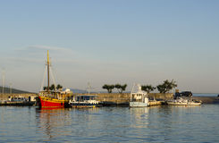 Red ship in a harbor. Small fishing boats in a harbor Royalty Free Stock Images