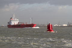 A red ship leaves port. In windy conditions. A red buoy shows the way Stock Image