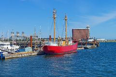 Moored red ship near pier at the bay in Boston. Red ship moored in the port in Boston, the United States. The Port of Boston is the major seaport in Royalty Free Stock Images