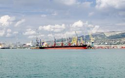 A seagoing ship on loading in the port. Red ship in the port on the background of the sky and mountains Royalty Free Stock Images