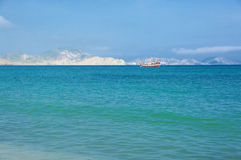 Red ship in sea against hills. Red ship in blue clear sea against sunlit hills Stock Photos