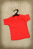 Red shirt on black hanger hanging on nail Royalty Free Stock Images