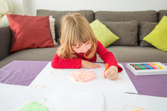 Red shirt child drawing with crayons. Three years blonde child red shirt with orange wax pencil or crayon in left hand drawing white sheet paper on table stock photo