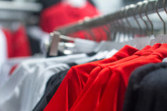 Red shirt hanging on a hanger in the store Stock Images