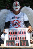 Red Shirt Protest. A street performer holds a sign while attending a red shirt protest outside the Thai Parliament on May 8, 2013 in Bangkok, Thailand. The Stock Photos