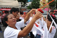 Red Shirt Rally in Bangkok. Red Shirt protesters tie paper cranes to a memorial while attending a large peaceful rally at Democracy Monument in remembrance of Royalty Free Stock Image