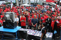 Red-shirts watching a video at a rally in Bangkok. BANGKOK - JANUARY 9: Red-shirt protesters watch a video of a political speech at a 30,000 strong anti Stock Photos