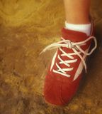 Red shoe. Clean, bright red lace-up shoe on foot wearing white sock (body or face not visible Royalty Free Stock Photography