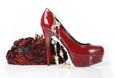 Red shoe, clutch bag and gold necklace. Burgundy shoe, clutch bag and gold necklaceon a white background stock images