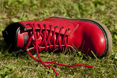 Red shoe. Red leather shoe lies on grass Royalty Free Stock Images