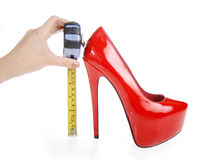 Red shoe and tape measure. On a white background stock image