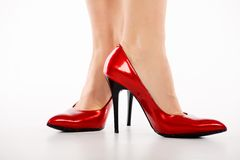 Red shoes. Female legs in elegant red shoes on white background Royalty Free Stock Photos