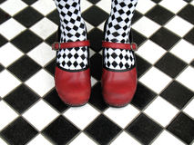 Red Shoes. And black and white checkered socks on checkered tile floor royalty free stock photo
