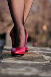 Red shoes. Female legs in black stockings and red shoes Stock Photo