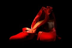 Red shoes. Dramatic light against black background Stock Image