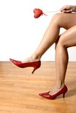 Red shoes. Woamn legs wearing red shoes and hand holding a red heart Royalty Free Stock Image