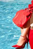 Red Shoes And Bag. Fashion - Accessories - Woman wearing red shoes with high heels and red bag, on the background of blue swimming pool Stock Photos